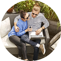 couple outside on couch with laptop