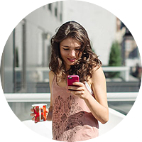woman holding beverage and cellphone